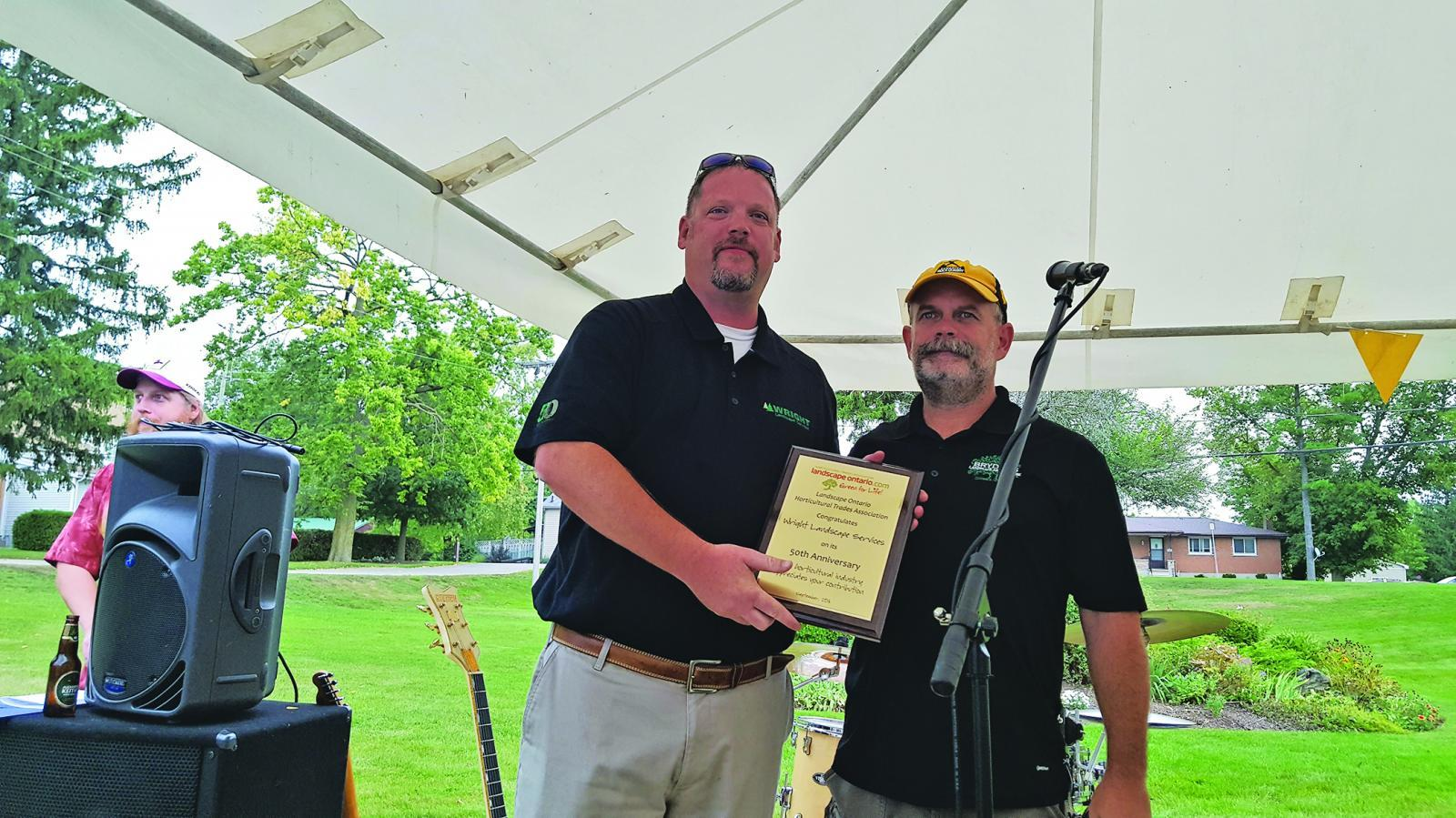 Dave Wright (left) accepts a plaque from LO President Paul Brydges.