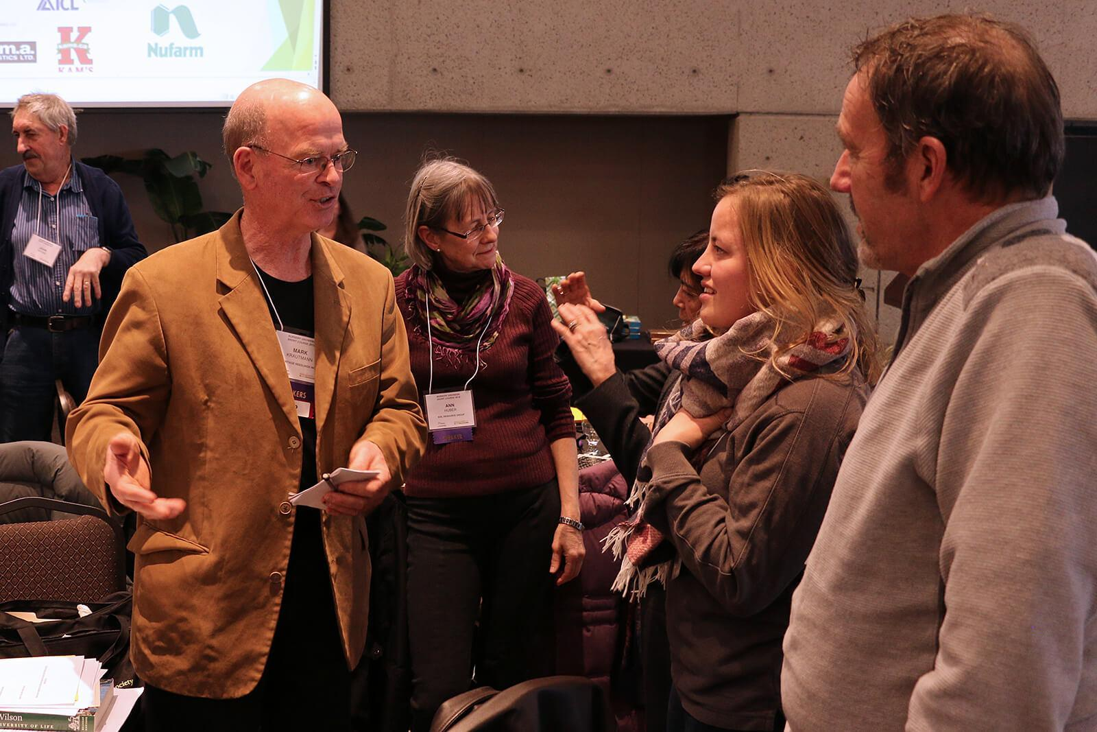 Keynote speaker, Mark Krautmann (left), talks with attendees during a break.