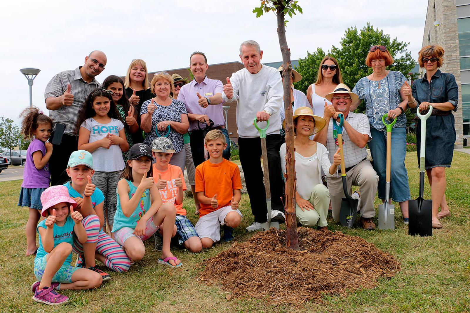 Milton Mayor Gord Krantz (centre with shovel) is surrounded by gardening enthusiasts during a Garden Days tree planting celebration at Milton Public Library.