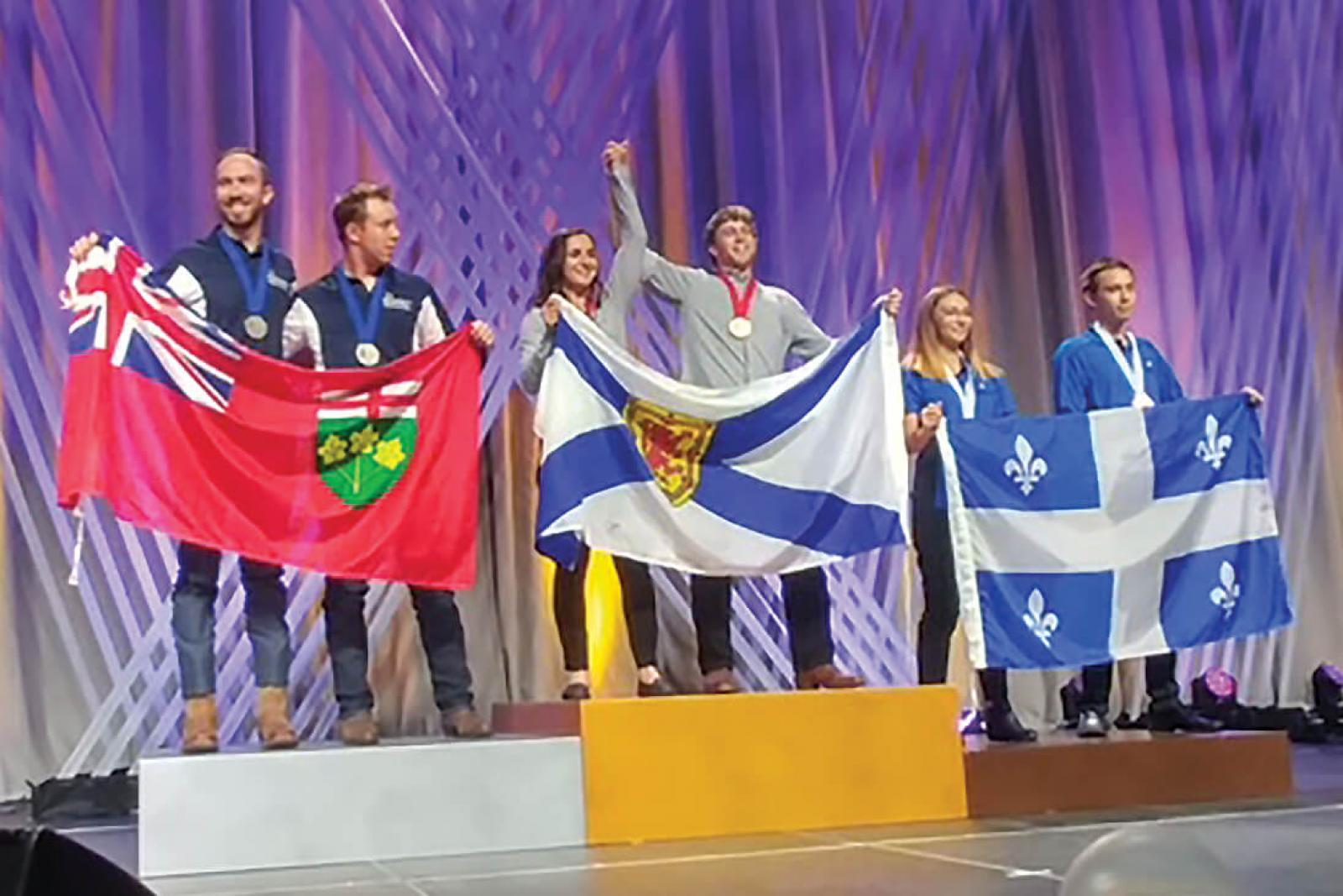 Algonquin College's Blaise Mombourquett (far left) and Thomas Hawley hold the Ontario flag atop the silver podium at Skills Canada 2018 in Edmonton, Alta.