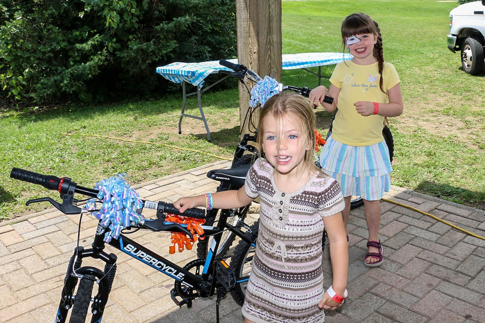 Eden Moriarty, 6 (back) and Brooke Garner, 4, held the winning raffle tickets and each took home a brand new bicycle courtesy of the Waterloo Chapter.
