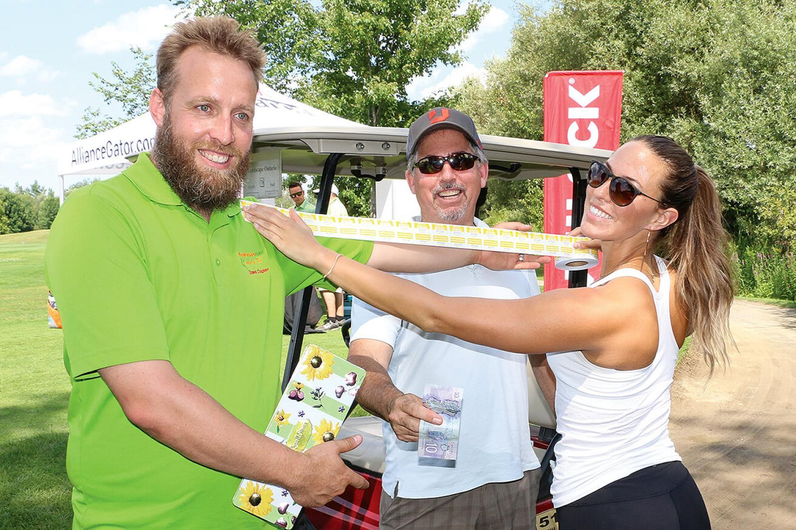 Golfer, Steve Low (centre), buys an arms length of raffle tickets from Ottawa Chapter Vice President, Lindsey Ross (left) and volunteer Olivia Urquhart.