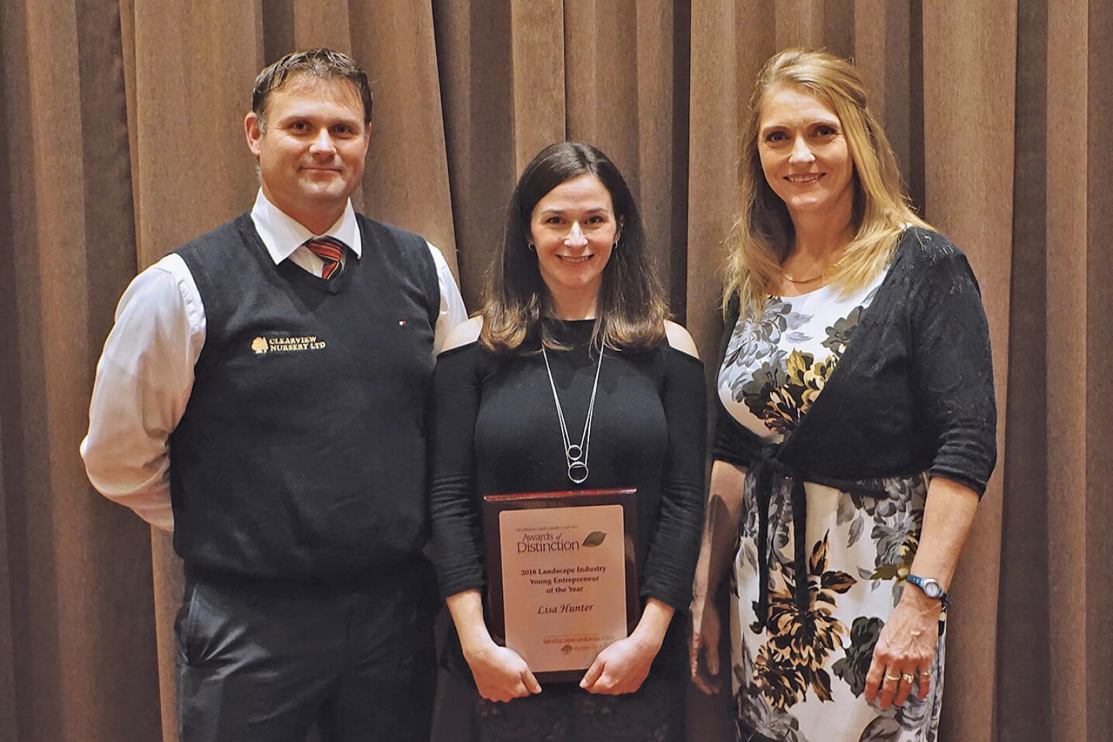 Michael LaPorte (left) and Laurie Ann Stuart (right) present Lisa Hunter with the chapter's inaugural Young Entrepreneur of the Year Award.