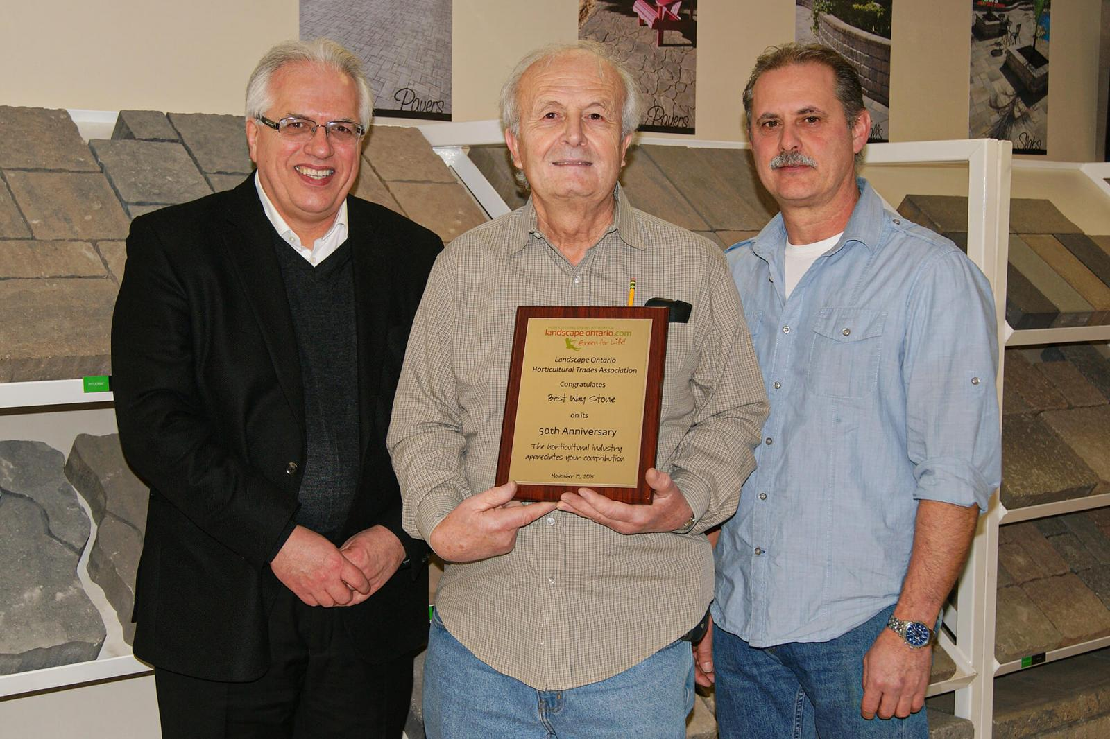 Landscape Ontario executive director Tony DiGiovanni (left) presented Frank Pacitto and Remo (Ray) Pignatelli of Best Way Stone with a commemorative plaque in honour of the company's 50th anniversary.