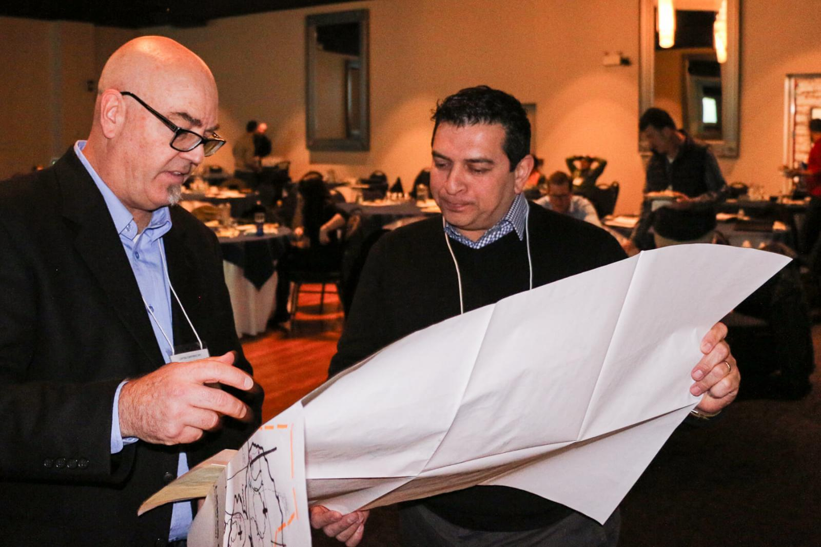 Event speaker Mark Carlson (left) shows one of his landscape lighting plans to Carl Hastings of Moonstruck Lighting.