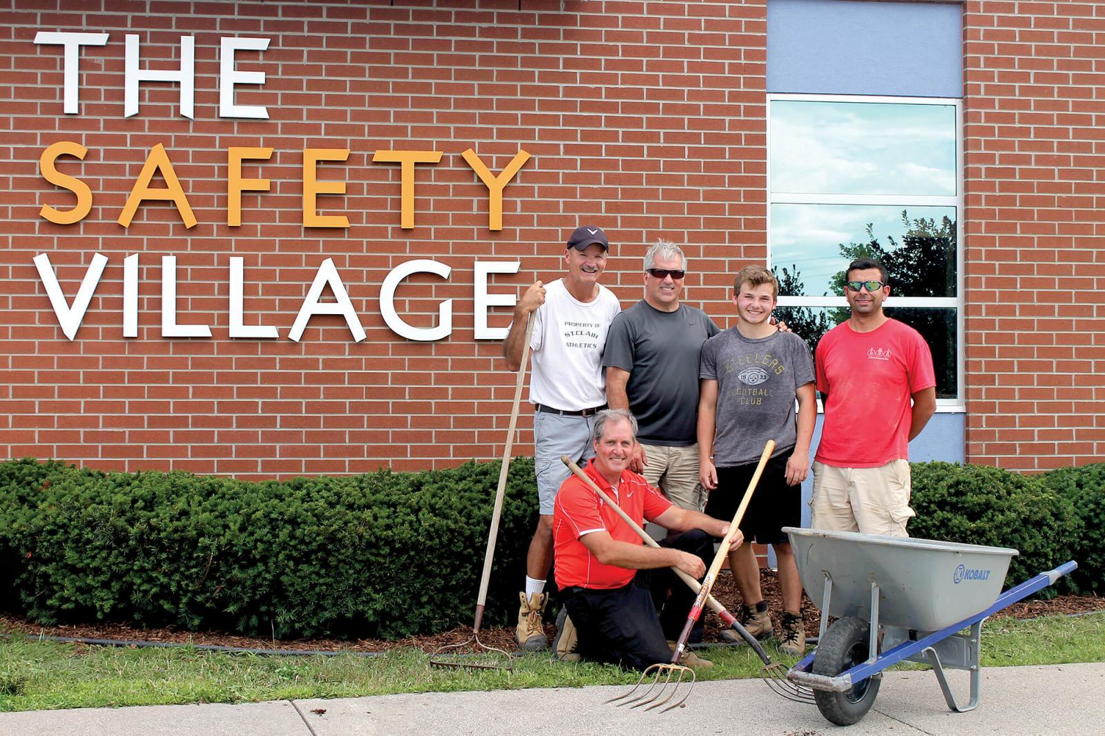 Volunteers from Windsor Chapter take a break from their work at Windsor Safety Village. In front is Garry Moore, with in back from left, Don Tellier, Chris Power, Mitchell Madej and Sal Costante.