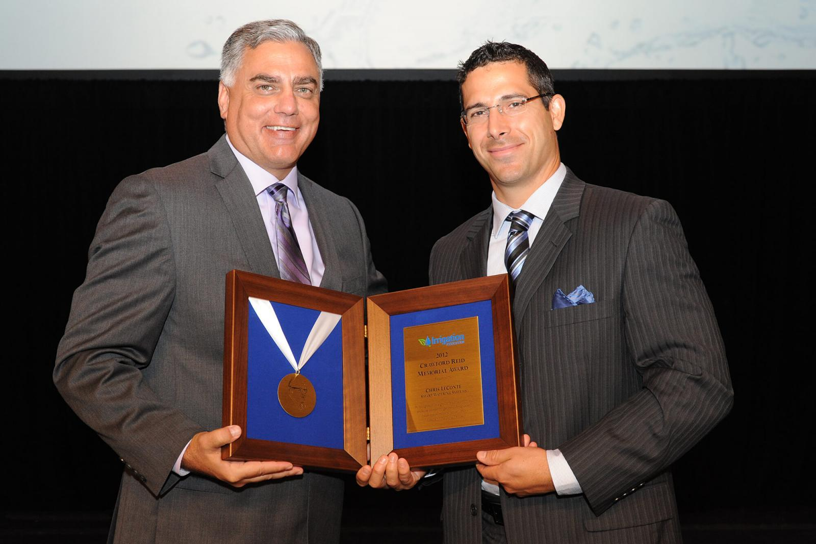 Toro president Phil Burkart, left, presents Chris Le Conte of Smart Watering Systems with the 2012 Crawford Reid Memorial Award.