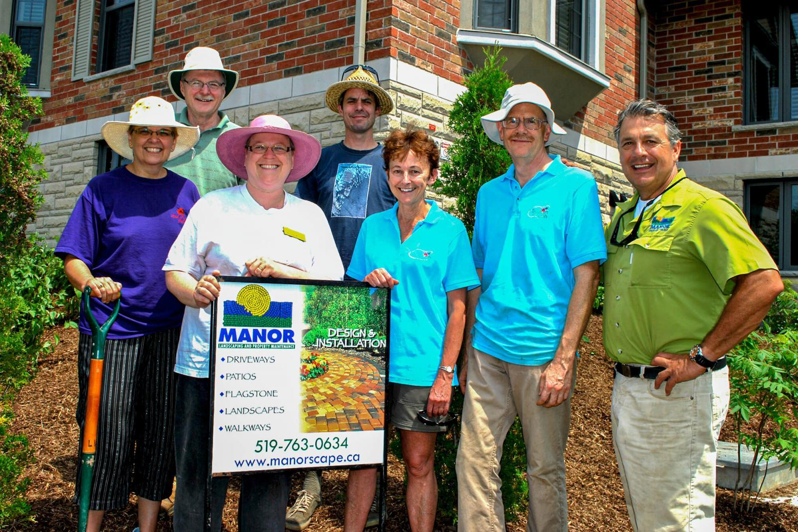 Volunteers praise Carlo Mann (right), owner of Manor Landscaping, for his support to beautify the grounds at the Guelph hospice.