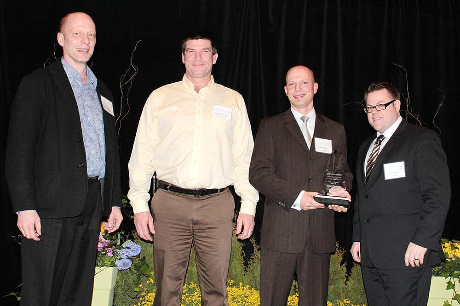 The Landmark Group of Thornbury received the Dynascape Award of Excellence for Landscape Design. In photo, from left, Mike Bosch, president of Dynascape; Gary Nordeman and Darren Bosch, both of The Landmark Group; and Joe Salemi, Dynascape product marketing manager.