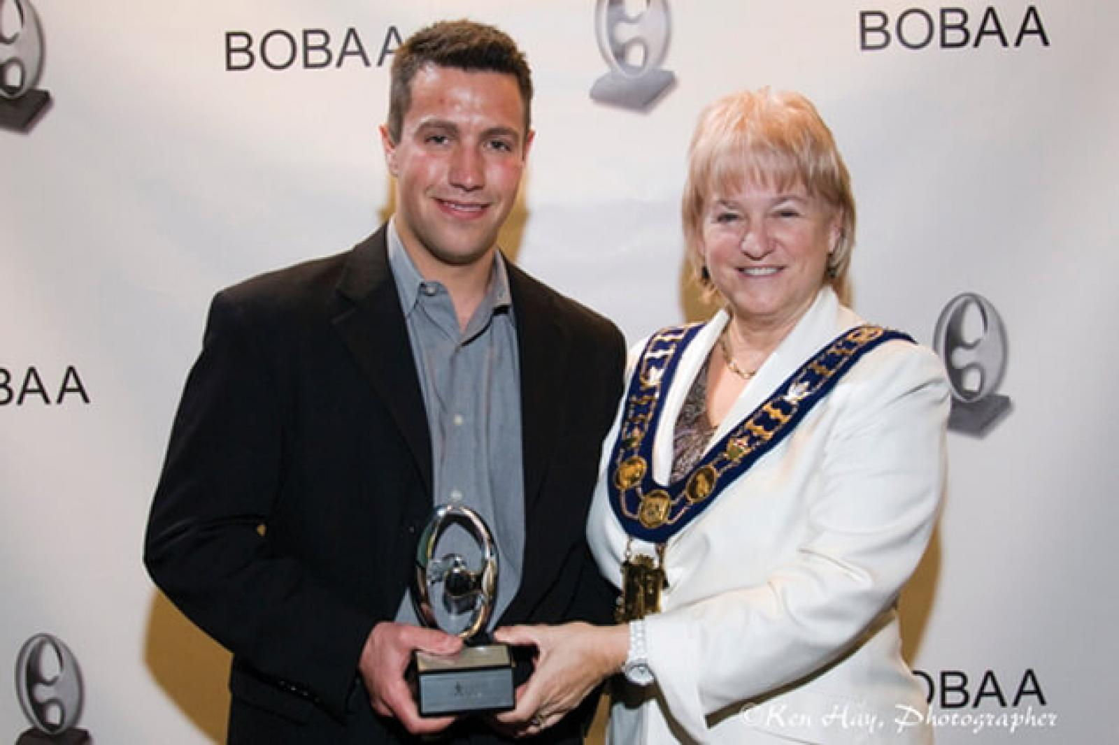 Matt Hill accepts the young entrepreneur of the year award from Brampton mayor Susan Fennell.