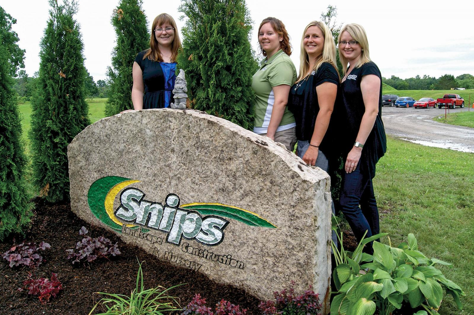 The ladies of Snips Landscape and Nursery, Alena Dawson, Tasha Beck, Kristi Montovani and Laura DeGraff, pose with what they call the tombstone, which greets visitors to Snips Landscape's 10-acre site just outside Welland.