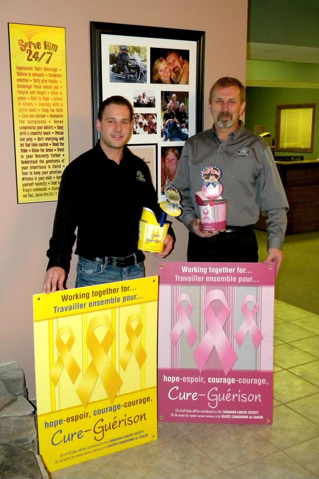 Michael Della Valle, left, and John Langendoen show the special pink and yellow pots, along with the posters available to garden centres.