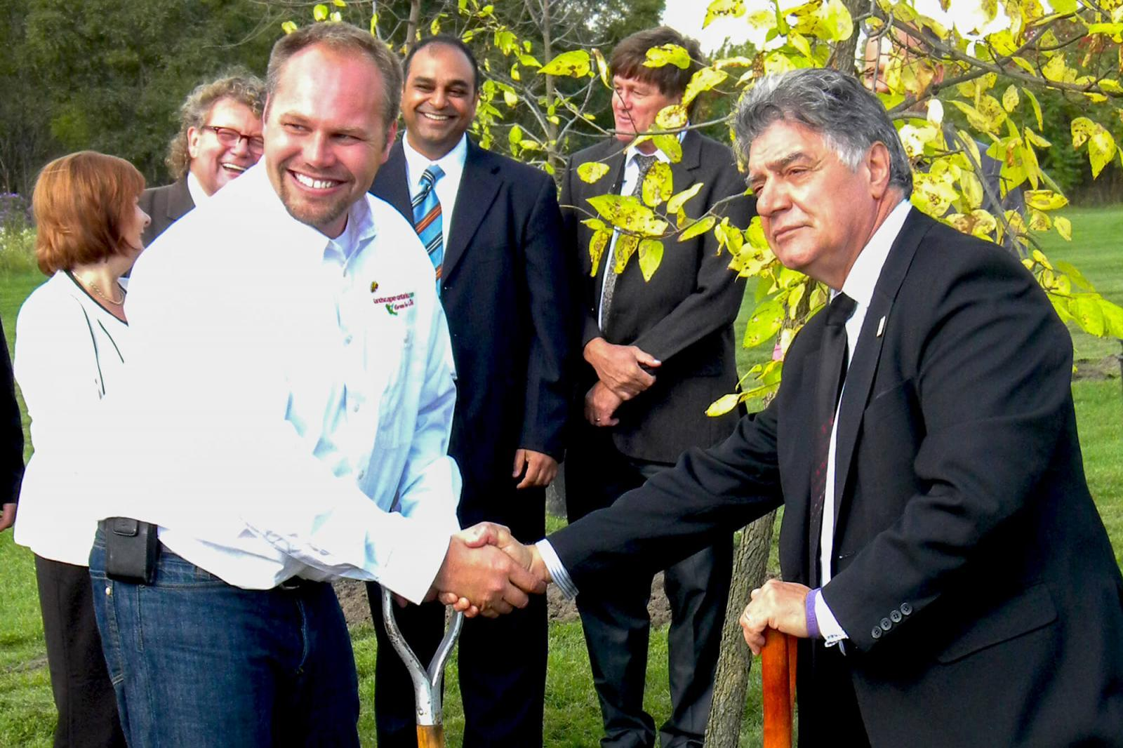 London Chapter president Grant Harrison and London mayor Joe Fontana plant the first tree as part of the Veterans Memorial Parkway project.