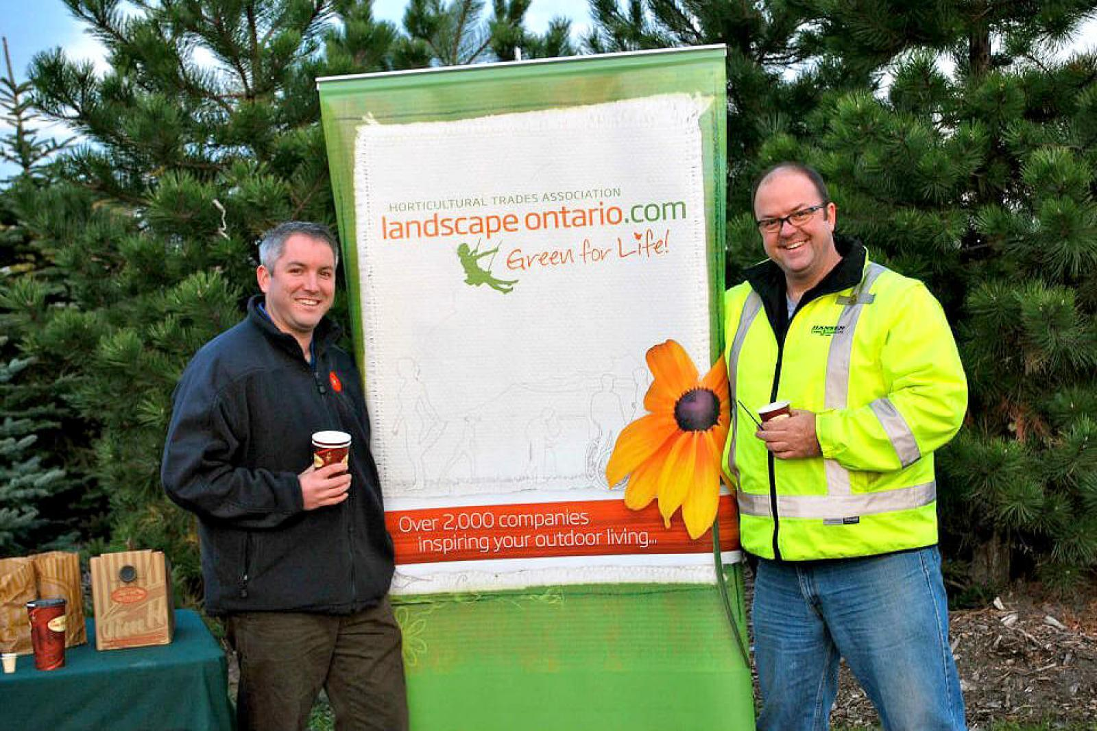 Chris Burns, president of the Ottawa Chapter and Clintar Landscape Management-Ottawa, on left, and Ed Hansen, vice president of the Ottawa Chapter and Hansen Lawn and Garden, take a break after volunteering at the Ottawa Cancer Survivors Park.