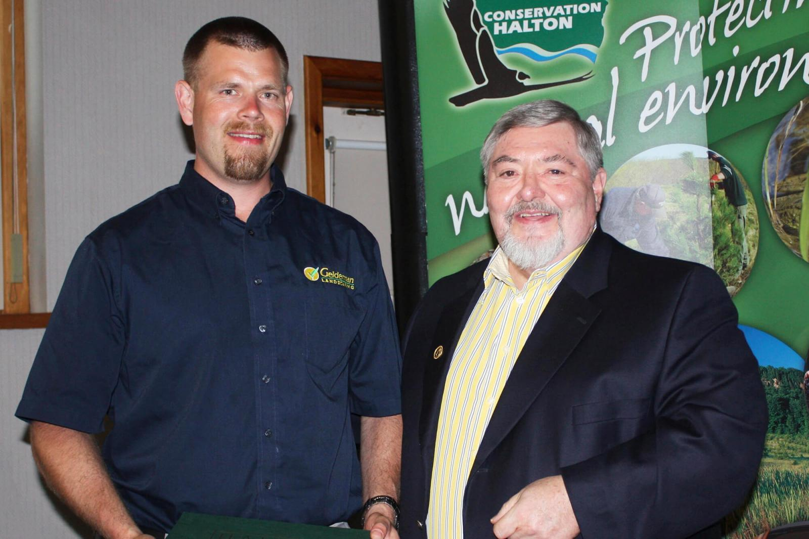 Nathan Helder, left, receives his award from Conservation Halton chair Brian Penman.