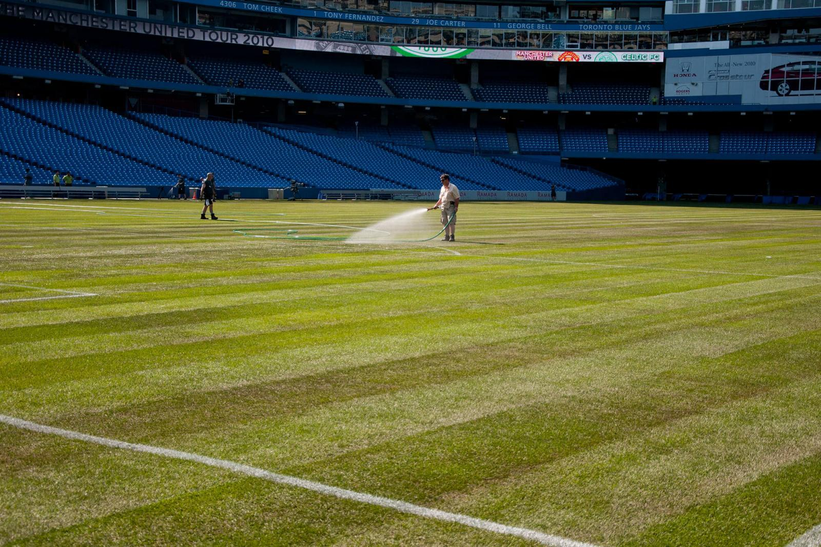 President of Greenhorizons, Ron Schiedel, puts water to the newly laid sod at the Rogers Centre, just before game time.