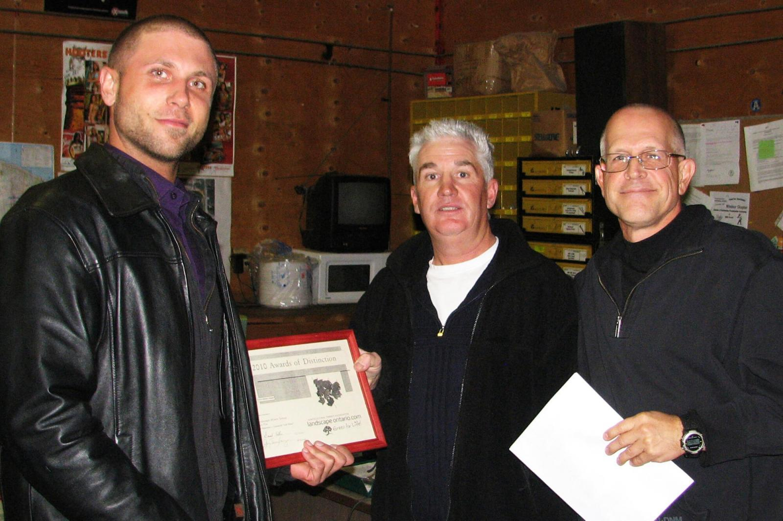 Chris Kaiser of the The Landscape Effects Group receives an award from Mark Williams and Jay Terryberry.