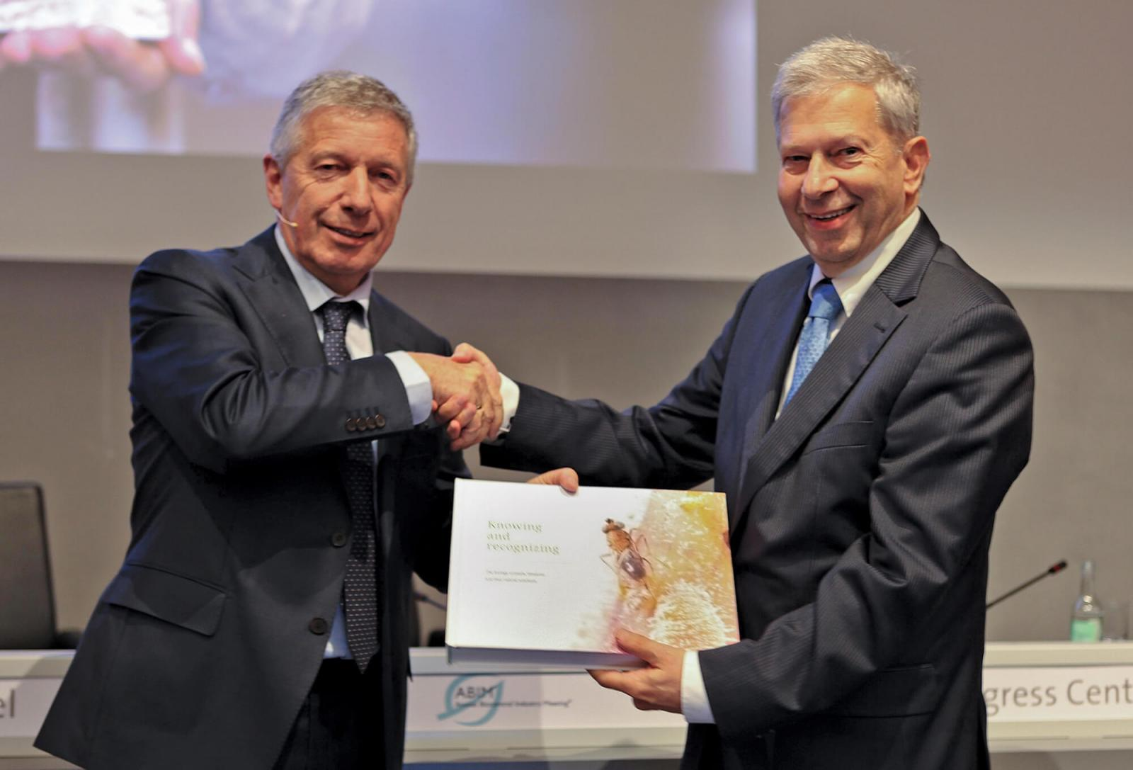 Kopperts Managing Director Paul Koppert presents  Willem Ravensberg, President of IBMA, with renewed  edition of Knowing and Recognizing.
